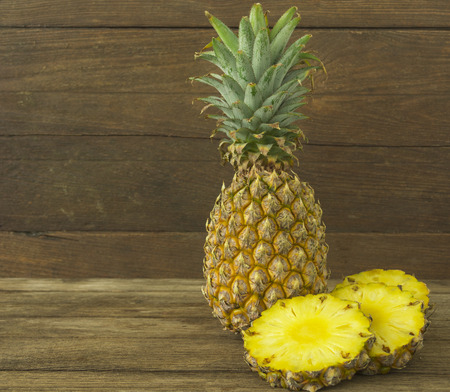 pineapple and pineapple slice on wood table