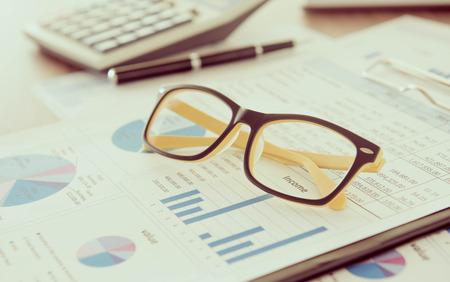 分析レポート、電卓、メガネをマーケティング担当者のデスク。