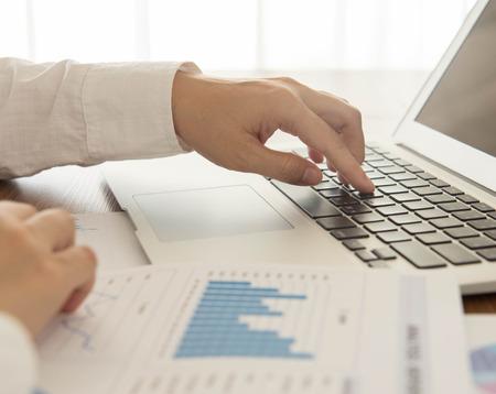 document management: Los hombres de negocios est�n analizando los datos de la computadora port�til y el informe.