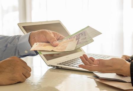 banco dinero: Los hombres de negocios est�n pagando intereses de los empleados del banco.