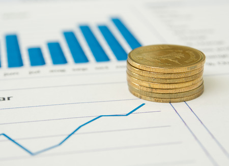 financial reports: Gold coins and financial reports.  investment concept.  selective focus. Stock Photo