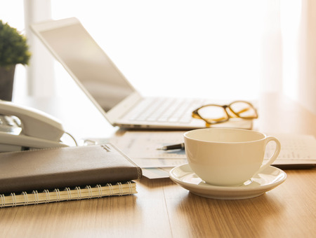 office stationery: Cup of coffee on the desk of the secretary. warm tone