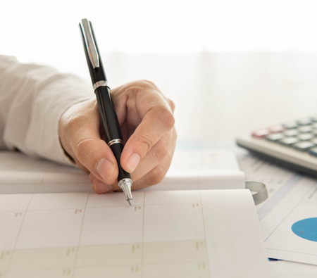 agenda year planner: businessman record data on  to schedule a meeting or event