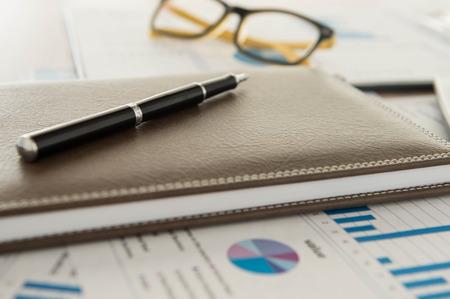 分析レポート、ペン、書籍のマーケティング担当者のデスク。 写真素材