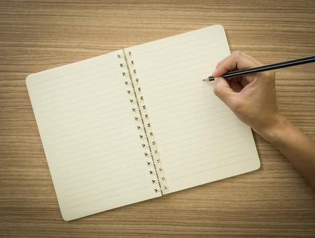 la main avec un crayon de prendre des notes dans un carnet