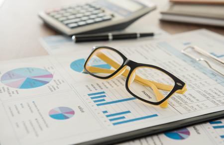 informe: Escritorio del vendedor con el informe de an�lisis, calculadora, gafas. Foto de archivo