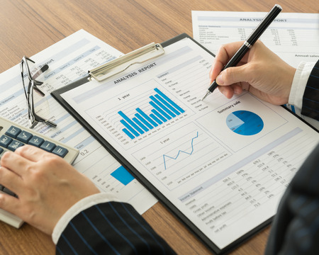 Businessmen are analyzing the data from the report. Stockfoto