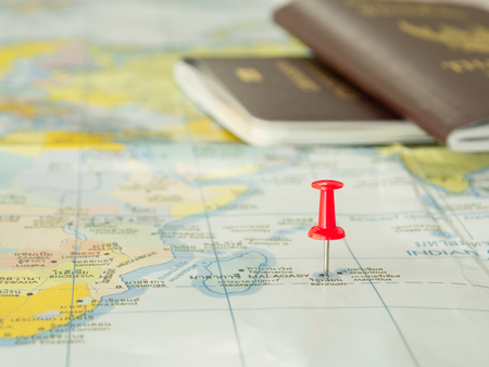 foto carnet: Bordado alfileres rojos en un mapa del mundo con un pasaporte