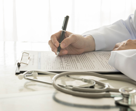 rx: close-up of doctor taking notes on hospital