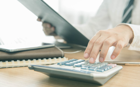 ビジネス: 実業家、数値を計算する計算機を使用して
