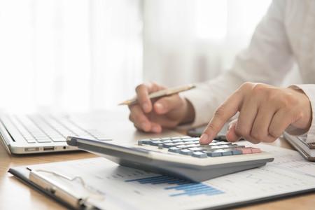 contabilidad financiera cuentas: Hombre de negocios usando una calculadora para calcular los n�meros Foto de archivo