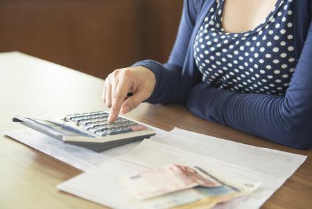 cuenta bancaria: Las mujeres son el cálculo de la calculadora para determinar el coste de la factura.