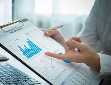 ビジネスマンは、データをクライアントまたはパートナーが知らされている市場を分析しています。