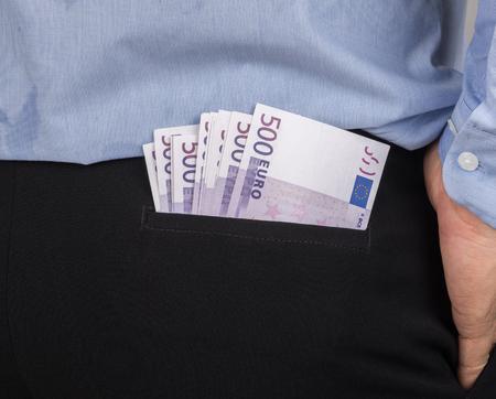 venal: human hide the money in the back pocket. corruption concept.