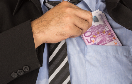 putting money in pocket: Businessman a putting money in his pocket Stock Photo