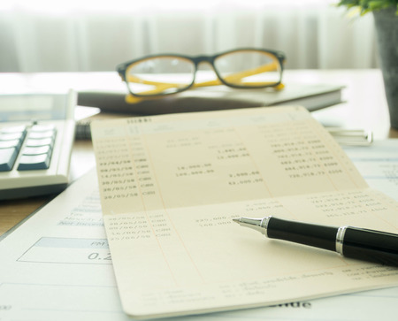 Accountants desk with pen and bank book. selective focus. Banque d'images