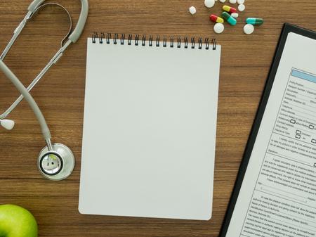 医師の机の上の患者のデータを記録するノート。