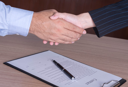 congratulate: businessman and businesswoman shaking hands to congratulate to be working well.