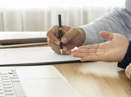 documentos legales: El personal recomienda los beneficios de la cobertura de seguro e invitar a los clientes a firmar un contrato.