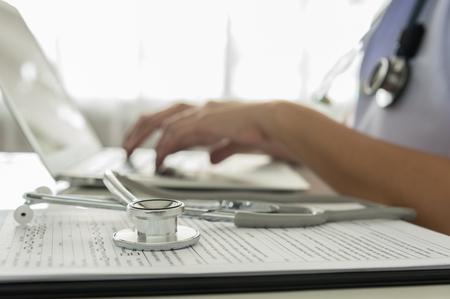 事務所でキーボードに入力する医者のクローズ アップ