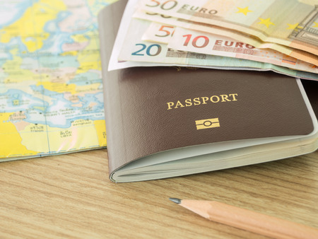 foto carnet: closeup passport on world map with banknote