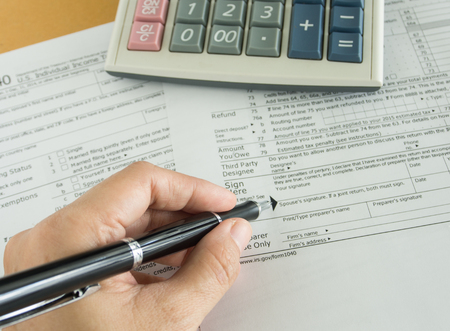 human hands will write in individual income tax return form