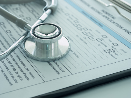 hospital notes: stethoscope with medical record application form on physicians desk