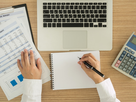 statements: Accountants are analyzing data from the financial statements of the Company. above view. Stock Photo