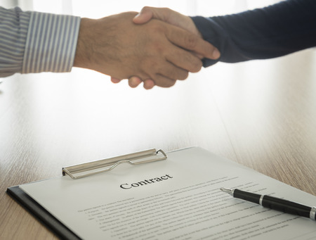 contracting: Documents contracting with partners are handshake background. select focus.