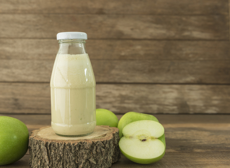 flavorful: green apple smoothie in bottle on wooden background