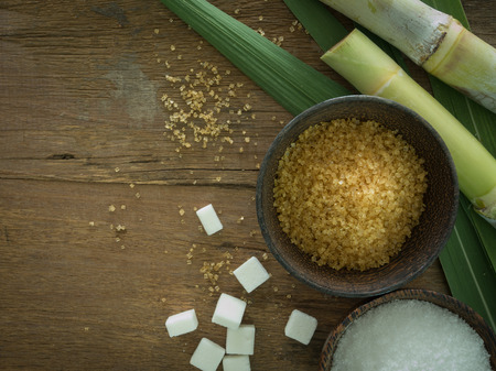 granulated  sugar with sugarcane stems on wooden background. above view. Stock fotó