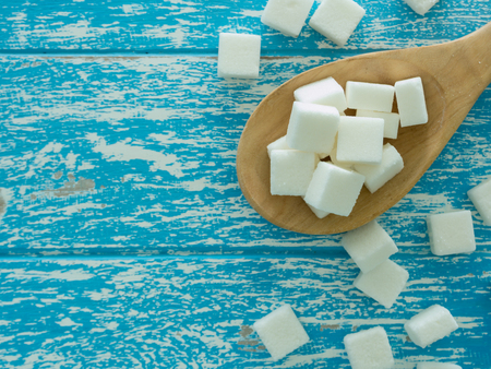 cube sugar on wooden spoon and  sugar on wooden background Foto de archivo