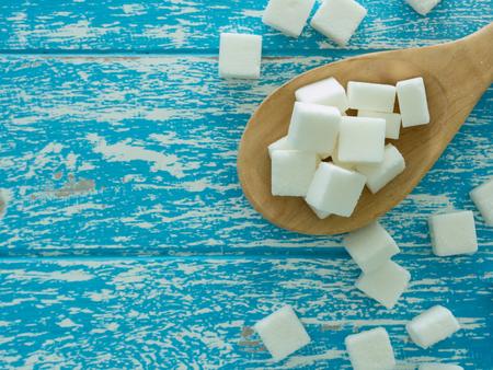 azucar: cubo de azúcar en la cuchara de madera y el azúcar en el fondo de madera