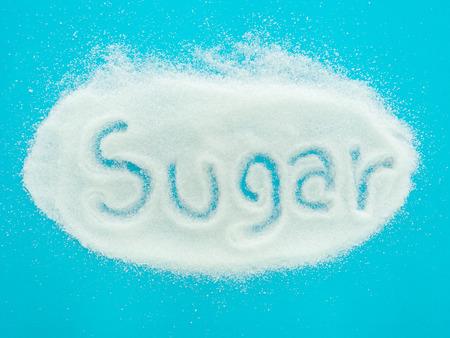 azucar: El az�car en la palabra escrita en un mont�n de az�car granulada sobre fondo azul. vista superior