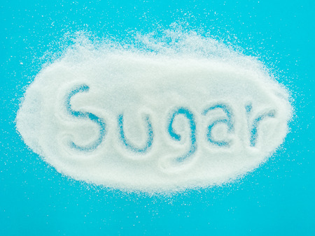 sugar cubes: The word sugar written into a pile of granulated sugar on blue background. top view