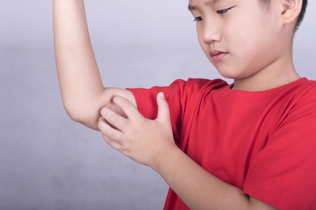 itch: Children scratch the itch with hand. Concept photo with Healthcare And Medicine.