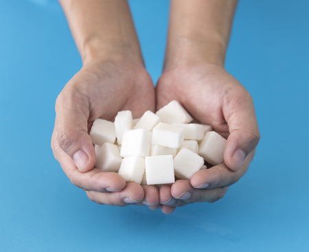 sugar cube: Human hand holding a sugar cube in hand with a blue background.