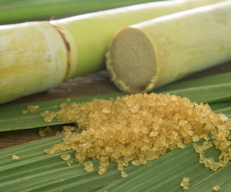 sugar cubes: closeup granulated brown sugar on sugarcane leaves. Stock Photo