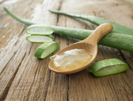 aloe vera gel on wooden spoon with aloe vera on wooden table