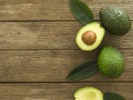 avocado and Sliced avocado slices on a dark wood background. 스톡 콘텐츠