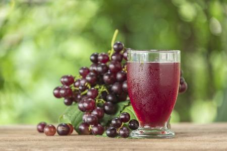 jugo de frutas: El jugo de uva en un vaso sobre la mesa. Foto de archivo