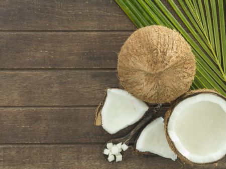 coco: Vista superior; fresca de coco y coco en rodajas sobre una tabla de madera. Foto de archivo