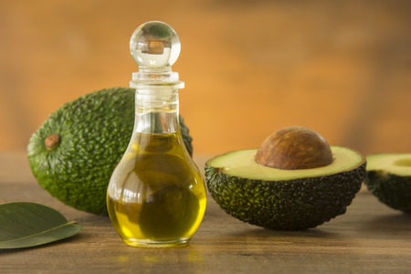 bottle of avocado essential oil with fresh avocado fruit closeup