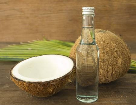 coconut fruit: coconut oil and fresh coconuts on wooden table. Stock Photo