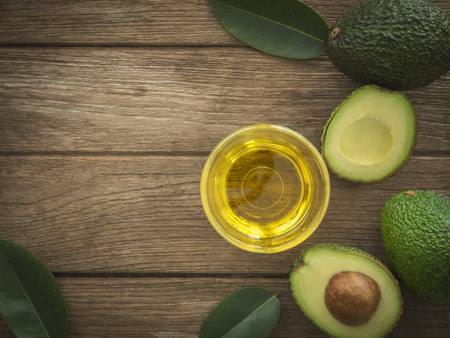 glass bowl of avocado essential oil with fresh avocado fruit closeup