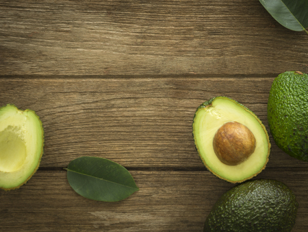 avocado and Sliced avocado slices on a dark wood background. Foto de archivo