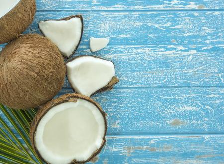 Świeże kokosowe i kokos w plastrach na drewnianym stole.