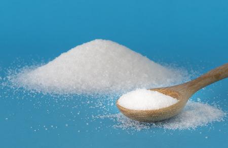 Cukier biały w drewnianą łyżką na niebieskim tle. Zdjęcie Seryjne