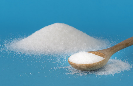 White sugar in wooden spoon on a blue background.
