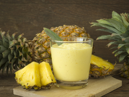 Pineapple juice and pineapple slice placed on a wooden table.